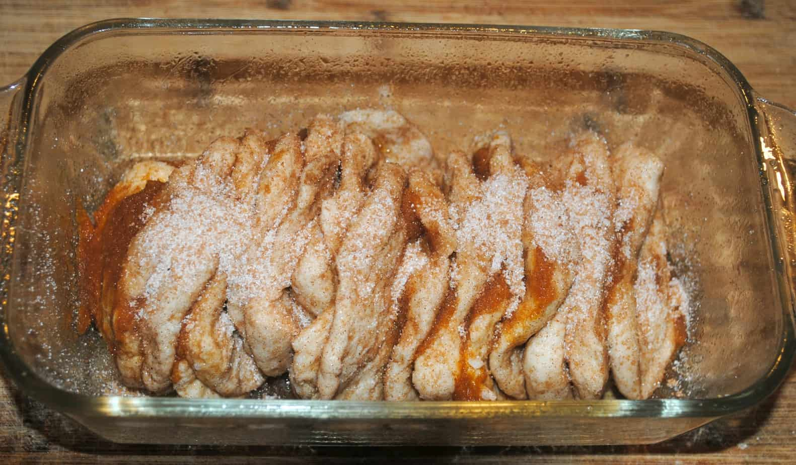 pumpkin-pull-apart-bread being put together in a glass loaf pan