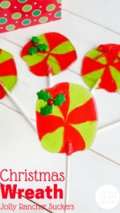 red and green jolly rancher suckers with a candy holly leaf at the top on a white table with title text reading Christmas Wreath Jolly Rancher Suckers