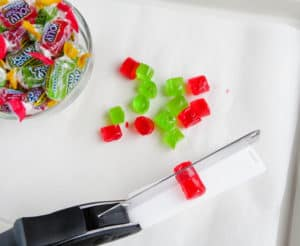 a bowl of jolly rancher candy, jolly rancher candy being cut in half by a clever cutter on a white paper