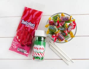 a bag of twizzlers, jar of holly candy, bowl of jolly rancher candy and sucker sticks on a white table