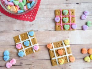 three graham crackers with pink frosting on it and candy conversation hearts to look like a tic tac toe board on a wood table with more candy next to it