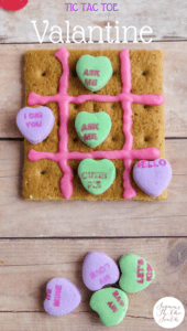 a graham cracker with pink frosting on it and candy conversation hearts to look like a tic tac toe board on a wood table with more candy next to it with title text reading Tic Tac Toe Valentine