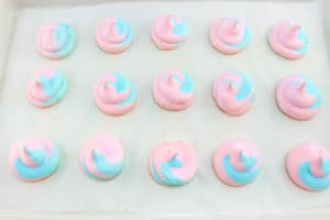 pink and blue meringues on a cookie sheet
