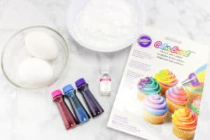 two eggs in a glass bowl, a white bowl of powdered sugar, a box of color swirl couplers, and food coloring on a counter
