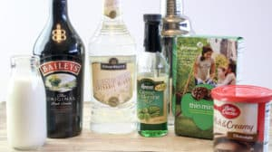 bottles of alcohol, box of thin mint cookies, container of chocolate frosting, glass of milk on a wood table