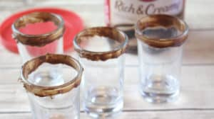 shot glasses rimmed with chocolate frosting with the container of frosting in the background on a wood table