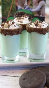 a close up of three thin mint shots in shot glasses rimmed with chocolate on a white plate on a wood table with a box of thin mints cookies in the background