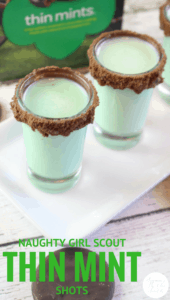 two thin mint shots in shot glasses rimmed with chocolate on a white plate on a wood table with a box of thin mints cookies in the background with title text reading Naughty Girl Scout Thin Mint Shots