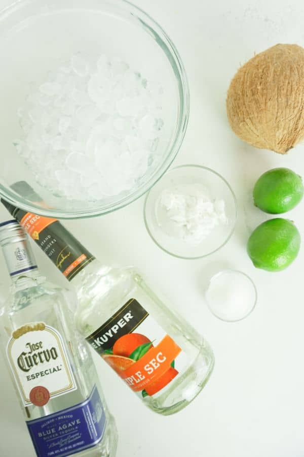 bottles of Tequila and Triple Sec, glass bowls of  Coconut Cream,  Sugar, and ice,  two limes and a coconut on a white table