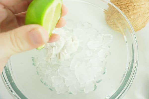 a hand squeezing lime juice over a glass bowl of ice on a white table with a coconut in the background