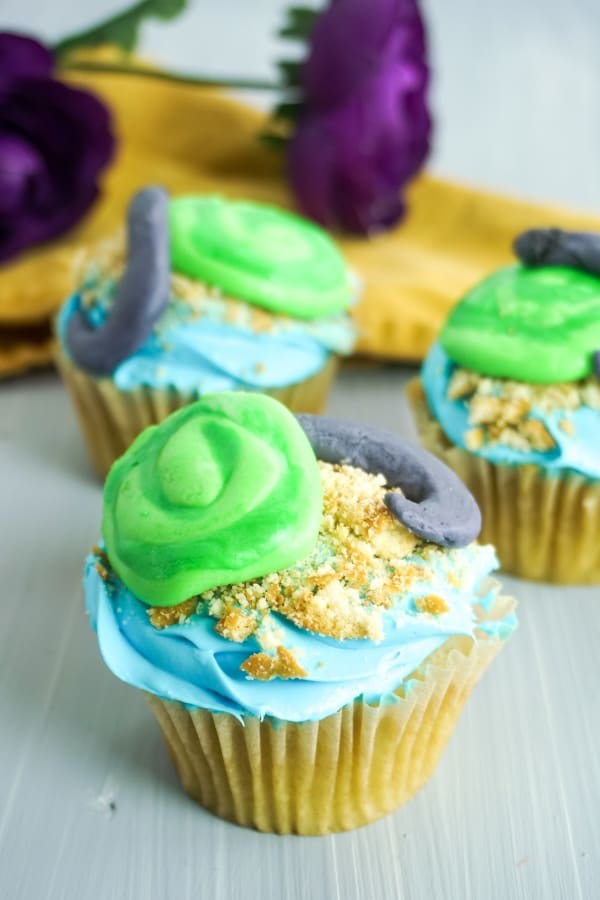 moana cupcakes decorated to look like the Heart of Te Fiti with green, blue and gray frosting on a grey background with yellow linen and purple flower in the background