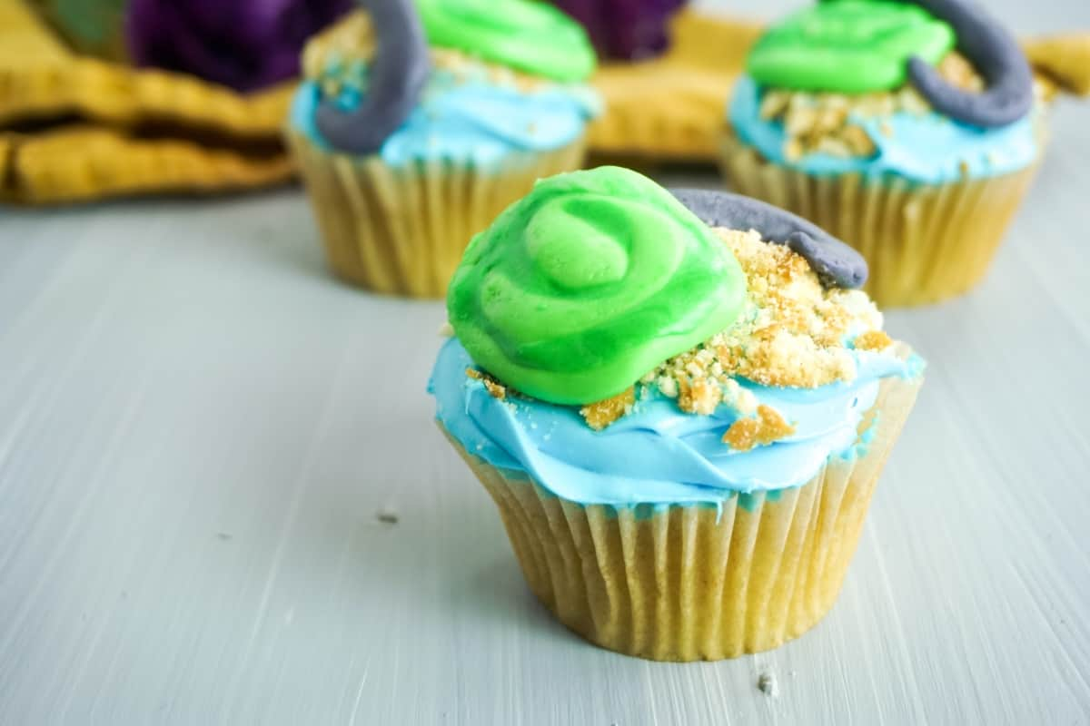 close up view of moana cupcakes decorated to look like the Heart of Te Fiti with green, blue and gray frosting on a grey background with yellow linen and purple flower in the background
