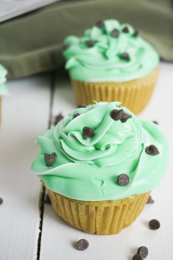 side view of two boozy mint cupcakes with chocolate chips on a white table and a green linen in the background