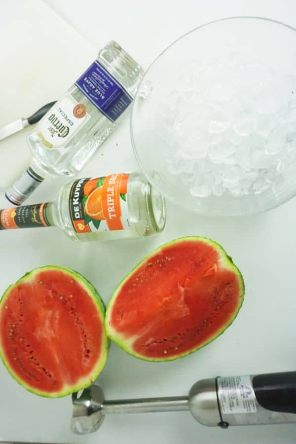 bottles of tequila and triple sec, a watermelon sliced in half, a glass bowl of ice, a knife and an immersion blender on a white counter