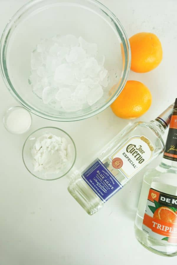 bottles of Tequila and Triple Sec, glass bowls of coconut cream, sugar, and ice, 2 oranges 2 cups ice on a white table