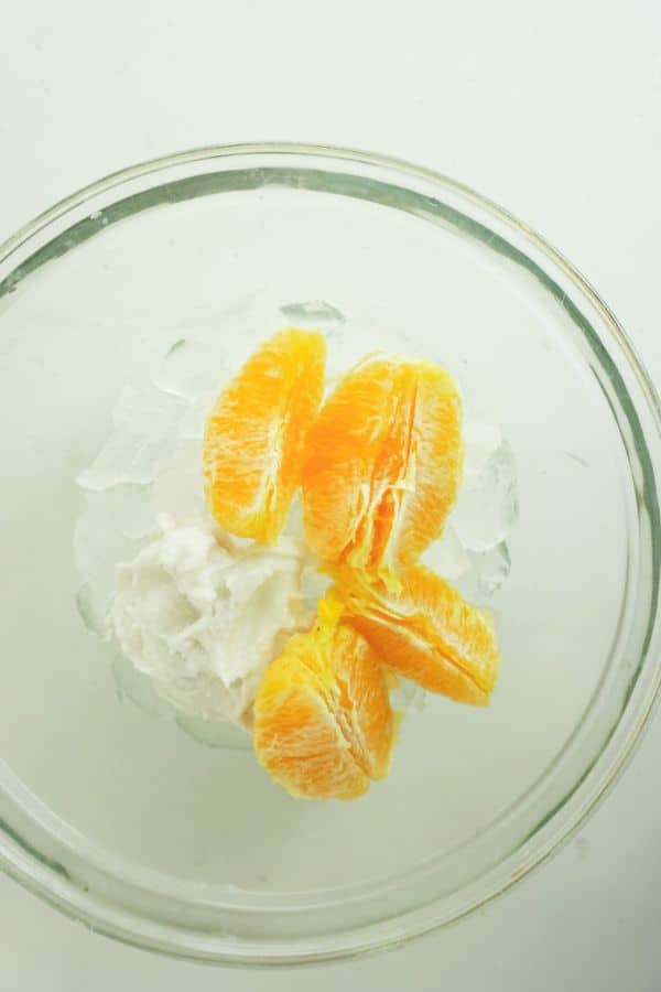 orange slices and ice in a glass bowl on a white table