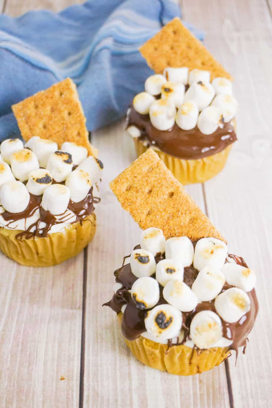 three cupcakes frosted with chocolate frosting topped with marshmallows and a graham cracker on a wood background with a muffin tin and blue linen in the background