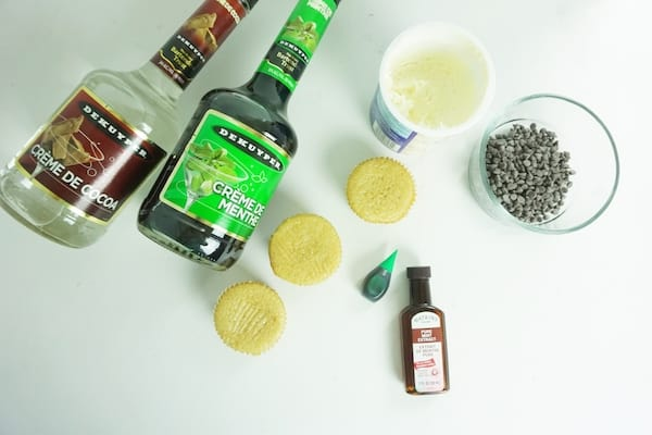 bottles of creme de cocoa and creme de menthe, three cupcakes, vanilla frosting, glass bowl of chocolate chips, green food coloring and mint extract on a white table