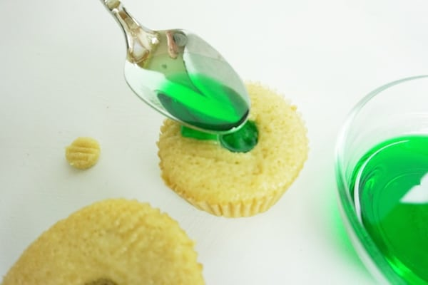 spoon filling a well in a cupcake with green liqueur mixture on a white table
