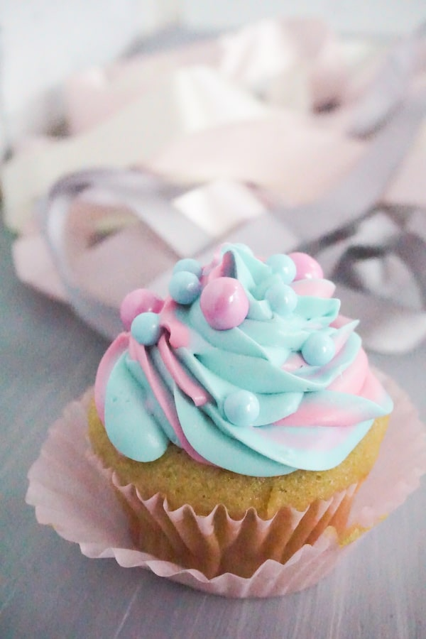 side view of a cupcake frosted with pink and blue frosting with pink and blue large sugar pearls on a grey table with white pink and grey ribbons in the background
