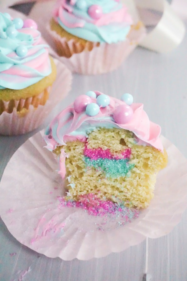 side view of cupcake sliced open and sprinkles spilling out on a pink cupcake liner on a grey table with cupcakes in the background