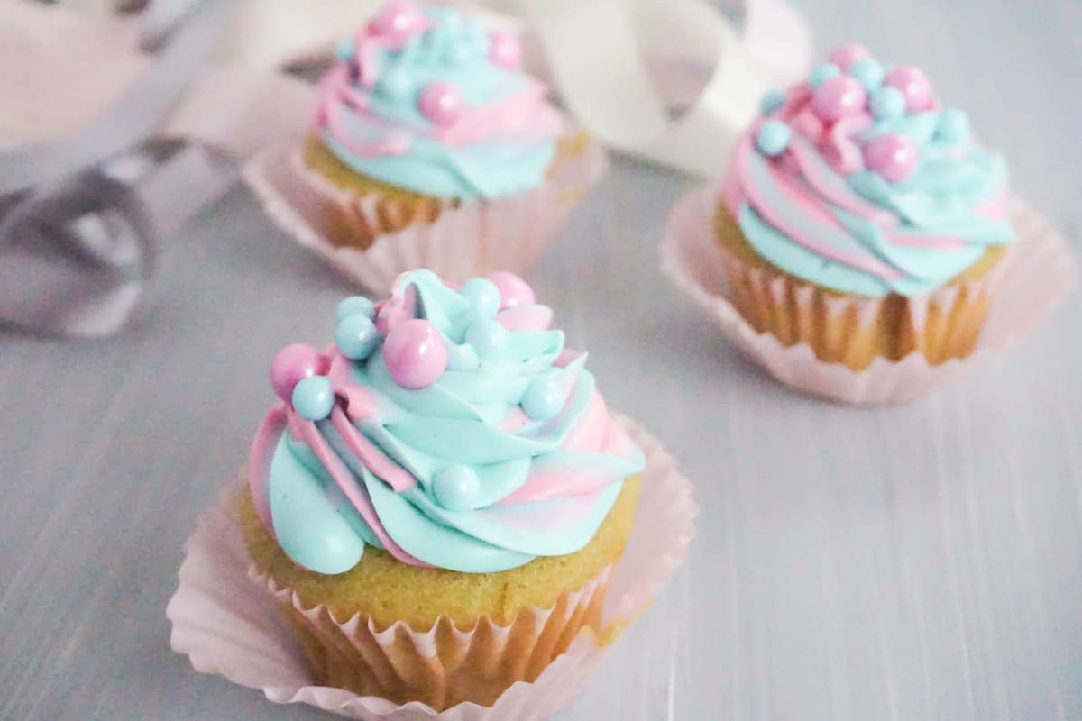 side view of three pink and blue swirled cupcakes with pink and blue large sugar pearls on a grey table with white pink and grey ribbons in the background