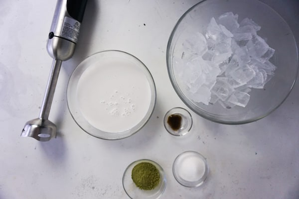 glass bowls of ice, cream, sugar, vanilla bean paste, match green tea powder and an immersion blender on a white table