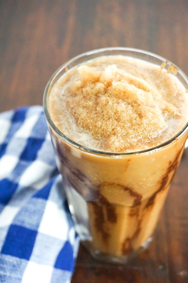 mocha frappuccino in a glass on a brown wood background next to a blue and white checkered linen