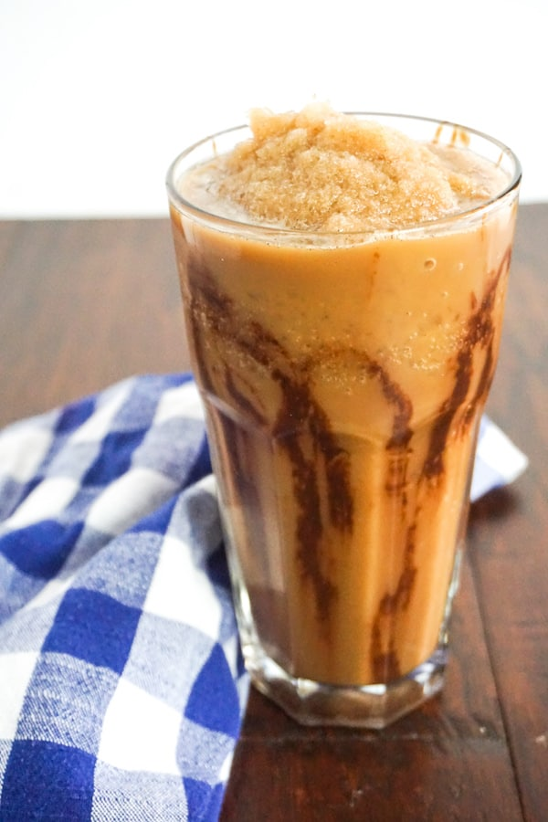 mocha frappuccino in a tall glass on a wood background with a blue and white checked linen