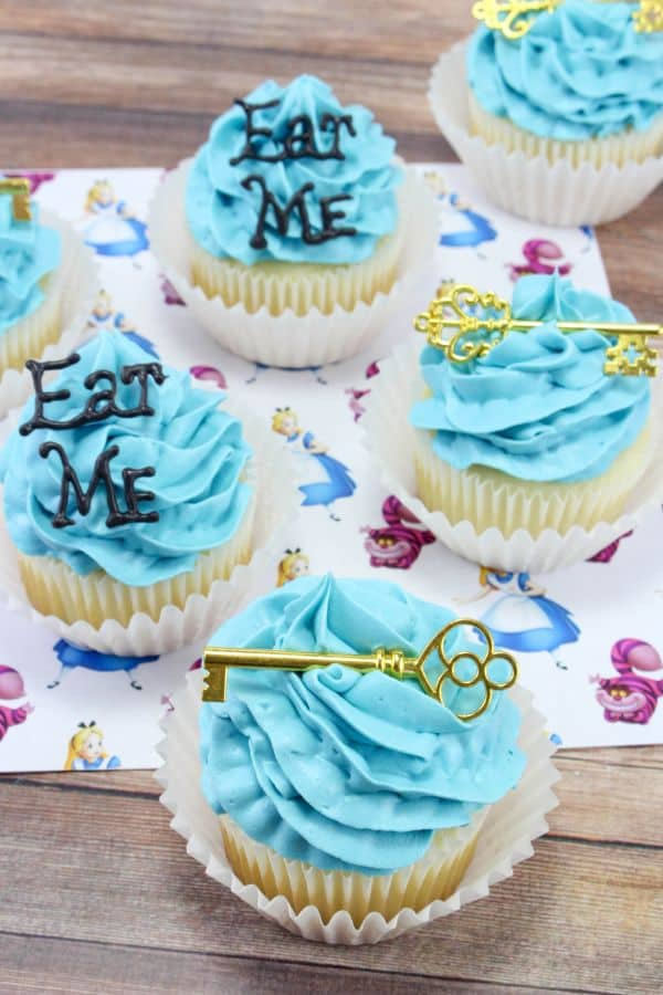 Alice in Wonderland Cupcakes with the words Eat Me on a couple of them and a gold key on a couple of them, all on an Alice In Wonderland paper on a wood table