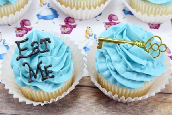 Alice in Wonderland Cupcakes with the words Eat Me on one of them and a gold key on one of them, all on an Alice In Wonderland paper on a wood table
