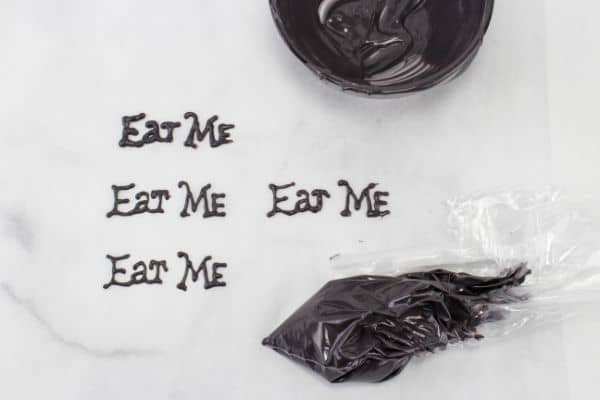 melted black candy discs in a bag being used to make the phrase Eat Me