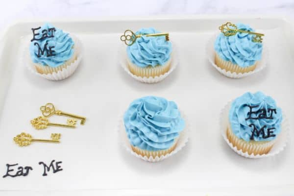 Alice in Wonderland Cupcakes with the words Eat Me on a couple of them and a gold key on a couple of them, all on a white baking pan