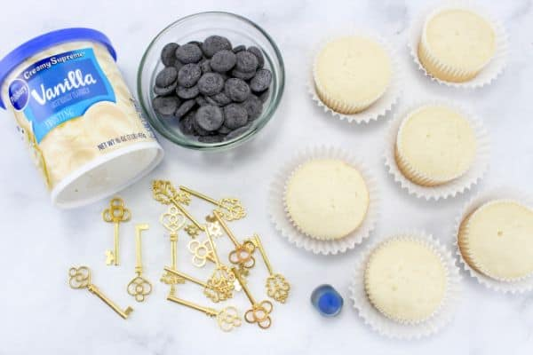 white cupcakes, vanilla frosting, wilton's black chocolate discs, gold keys, blue food coloring on a gray background