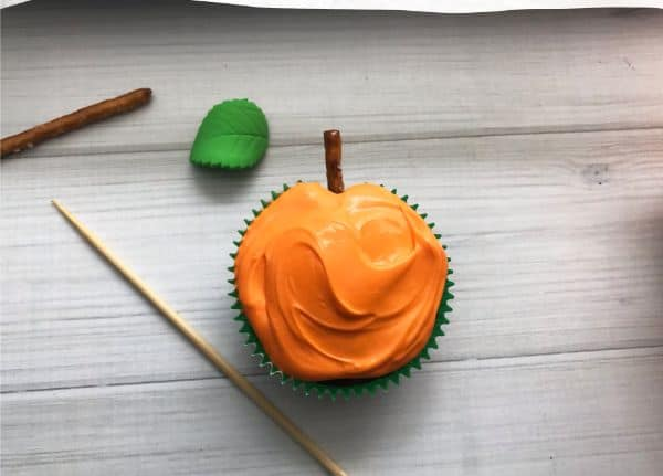 a cupcake with orange frosting and a pretzel stick as a stem next to a skewer, candy leaf, and pretzel stick on a gray wood table