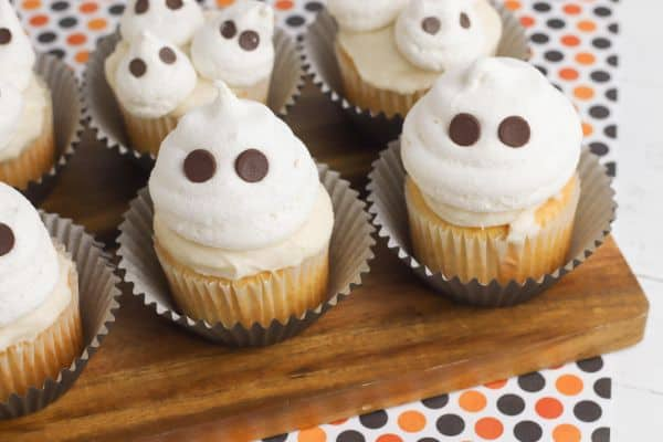 cupcakes topped with vanilla frosting and a meringue cookie with chocolate chips in it so it looks like a ghost with eyes, all on a wood slat