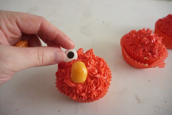a hand placing a candy eye next to an orange starburst nose on a cupcake decorated with red frosting on a white counter with two more cupcakes in the background