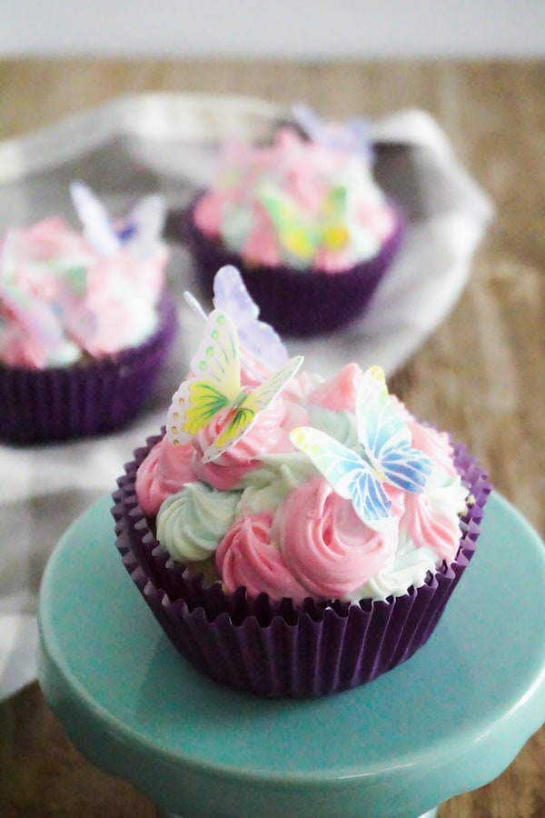 a cupcake with pink and green frosting with edible butterflies on top, on a green cake stand on a brown table with two more cupcakes in the background on a linen