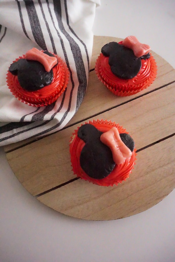 three cupcakes decorated with red frosting, black fondant to look like Minnie Mouse and a pink Starburst shaped to look like a bow, on a wooden trivet on a gray and white cloth, on a white background