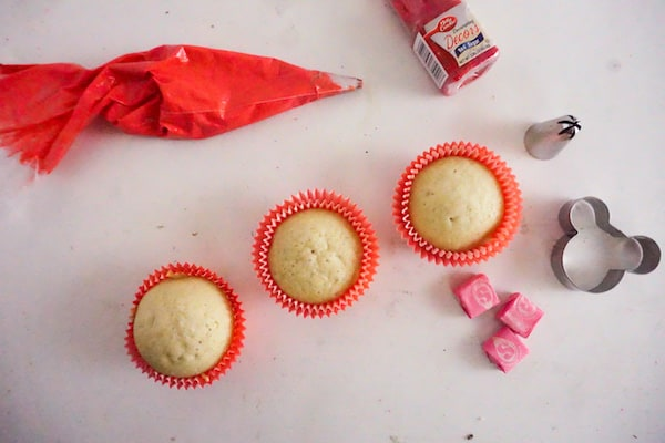 three vanilla cupcakes in red cupcake liners, red frosting in a pastry bag, red sprinkles, a piping tip, minnie mouse cookie cutter, three pink starbust candies, all on a white background