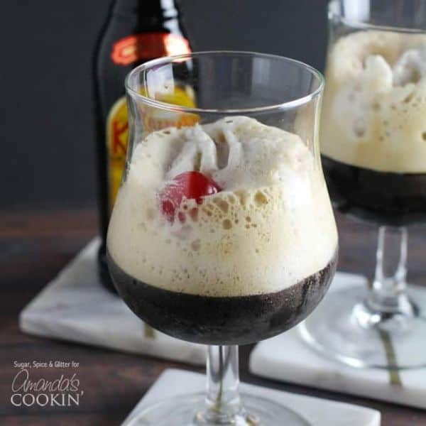 Kahlua frappuccino in a glass topped with foamy cream and a cherry with a kahlua bottle in the background