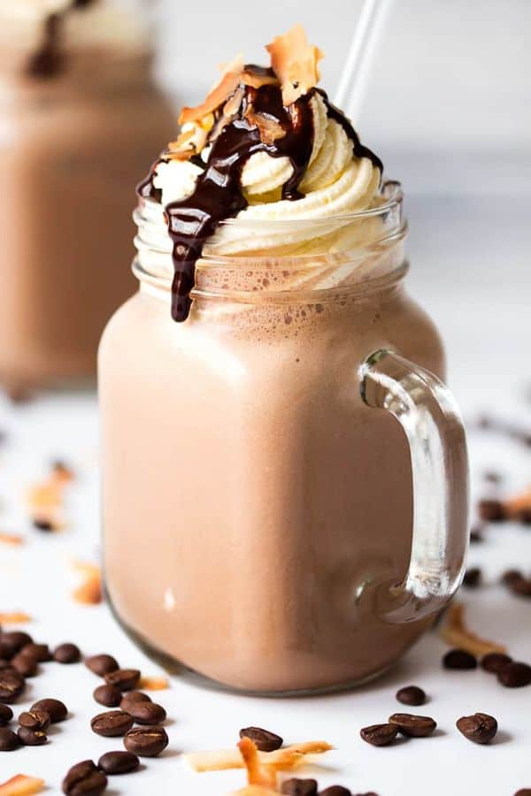 Mocha coconut frappuccino in a glass mug topped with whipped cream, chocolate syrup, and coconut with a straw in it. Another drink is in the background and coffee beans are on the table.