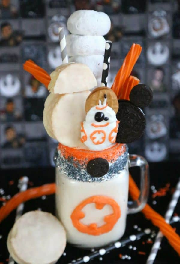BB-8 Star Wars Freak Shake in a glass topped with oreos, nutter butters, mini powdered donuts, and orange twizzlers on a black table