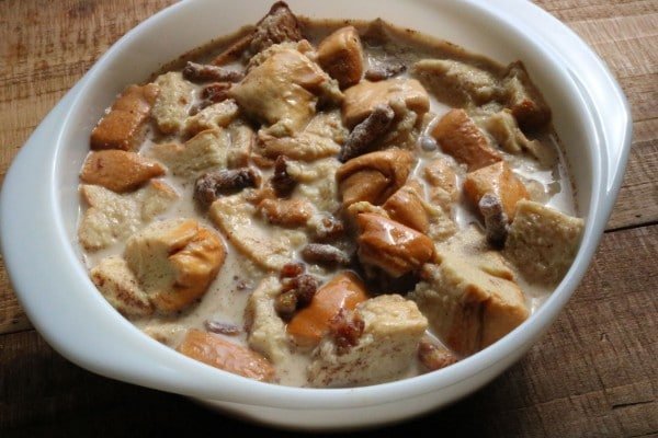 bread pudding in a white casserole dish on a brown table