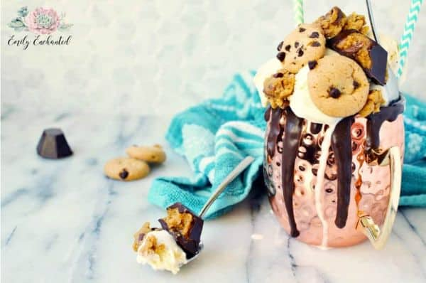 chocolate chip cookie dough freak shake tipped with cookies and chocolate sauce on a counter with a blue towel in the background