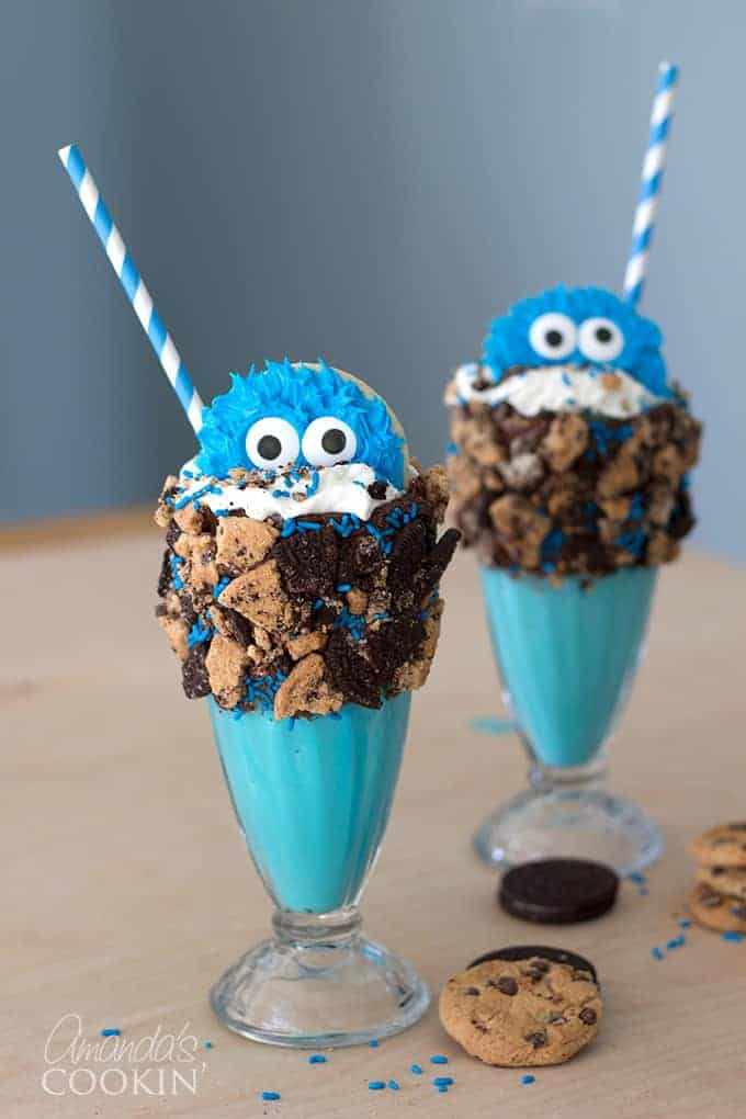 cookie monster freakshake in two glasses topped with a cookie monster cookie