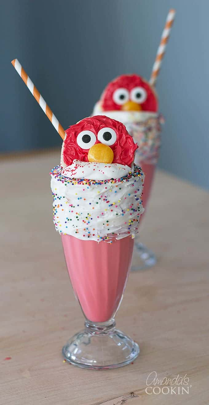 elmo freakshake in two glasses tipped with whipped cream and sprinkles and an elmo cookie on a brown table