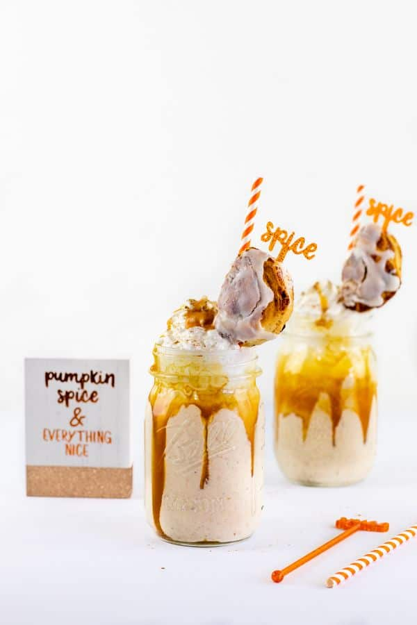 pumpkin pie freak shake in two glasses topped with half a cinnamon roll on a white table with a sign reading pumpkin spice and everything nice