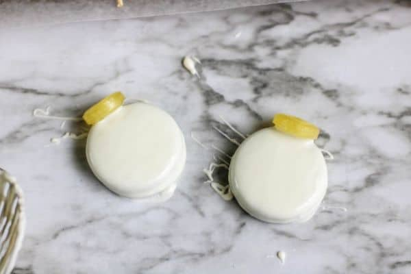 tow oreos dipped in white chocolate with a yellow lifesaver on the top all on a kitchen counter