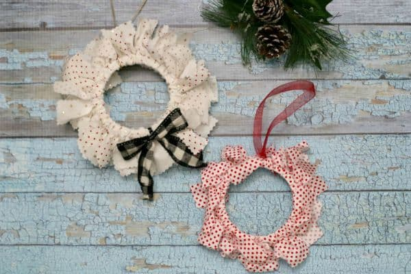 Two fabric mason jar lid ornaments (one white and one red) on a plank table next to a green bough with pine cones.